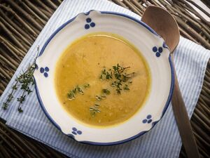 Soup of squash roasted with garlic and thyme, served in blue and white bowl with