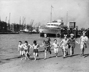 Summer at last, children running on the beach by the Tower of London. The pleasure