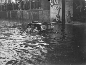 Swimmers around submerged vehicles in the greatest recorded floods in Kingston, the