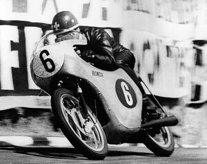 Switzerland's Luigi Taveri riding a Honda, speeding out of the dip at Governor's