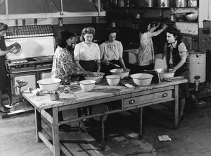 Teaching young women cooking in a kitchen 1950s