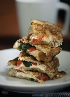Toasted sandwich of gluten free bread with goat's cheese feta, tomatoes and basil