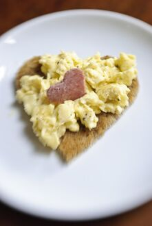 Valentine's day breakfast of scrambled eggs on heart shaped toast with slice of salami