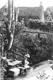 A Victorian girl fetching water from a stream at the bottom of the garden