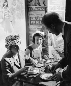 A waiter serves two ladies at lunch in Le P'tit Monmartre, Marylebone Lane, London