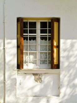 Window in white house in dappled sunlight with white embroidered cutwork curtain