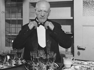 A wine waiter fixes his bow tie. undated