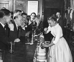 A woman barmaid pulls a pint of beer for male customers in a London pub , England. 1950s