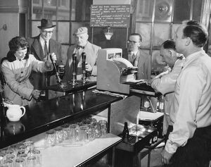 A woman customer pulls her own pint of beer at The Elephant and Castle, London, England