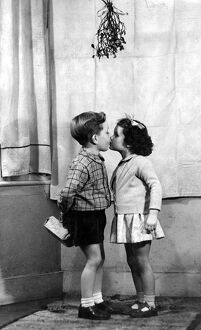 Young boy and girl kissing underneath the mistletoe at Christmas time 1956 love