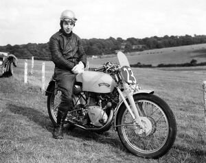 A young John Surtees sitting astride his Vincent motorbike at a race track