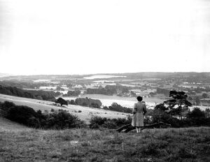 A young woman admires a view across the Weald of Kent